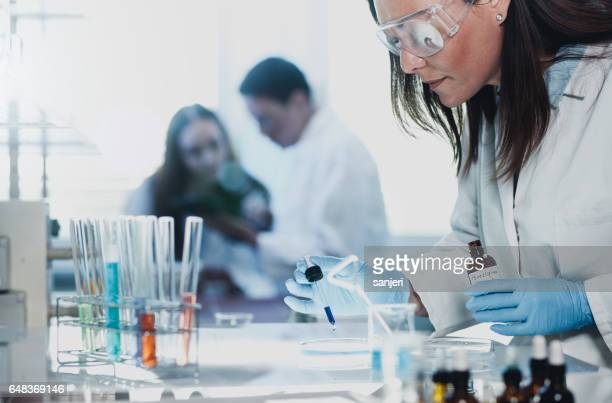 Scientist Placing a Reagent into a Petri Dish
