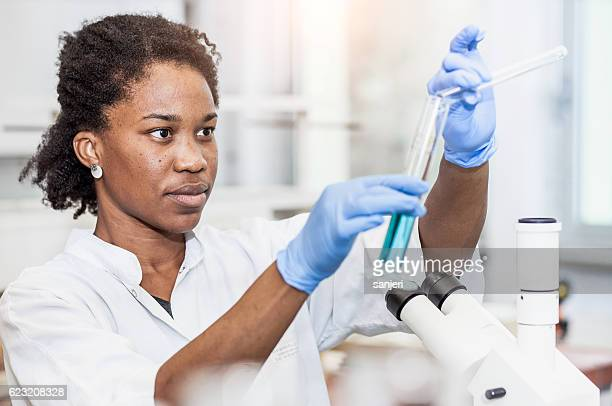 Scientist pouring a chemical into a measuring cylinder
