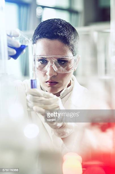 Scientist pouring a reagent into a measuring cylinder