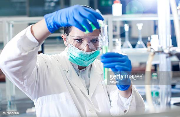scientist pouring a reagent into a measuring cylinder - volume fluid capacity stock pictures, royalty-free photos & images