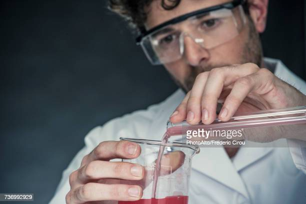 Scientist pouring liquid from test tube into beaker