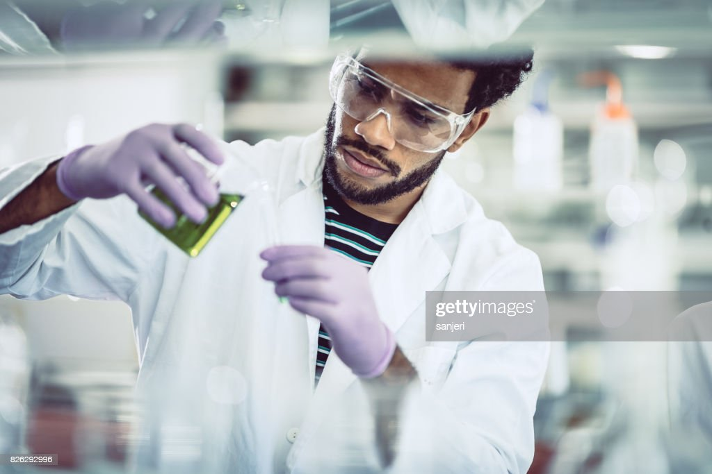 Scientist Pouring Reagent into Test tube : Stock Photo