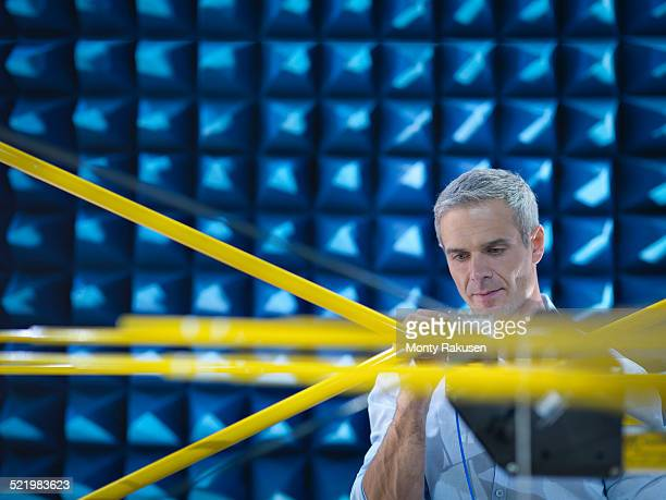 Scientist preparing to measure electromagnetic waves in anechoic chamber, close up