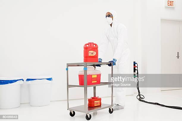 Ein Wissenschaftler Schieben eine trolley mit chemischen Abfälle auf Sie