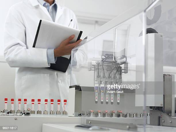 Scientist recording data from test tubes in machine
