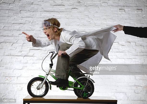 Scientist Riding Mini Bike While Person Grabs His Lab Coat
