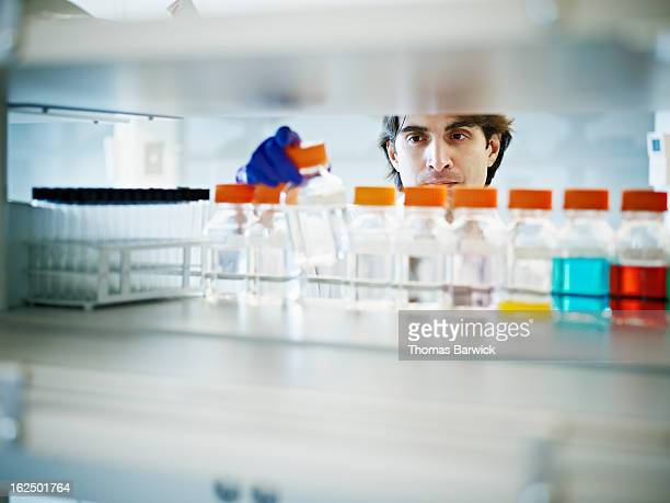 Scientist selecting bottle of solution in lab