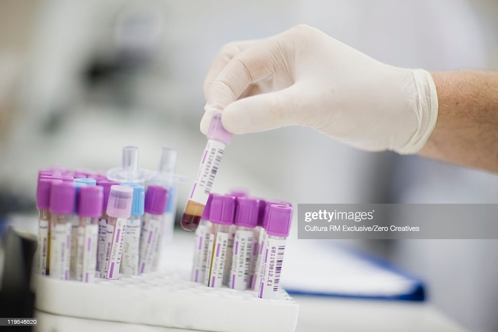 Scientist selecting test tube in lab : Stock Photo