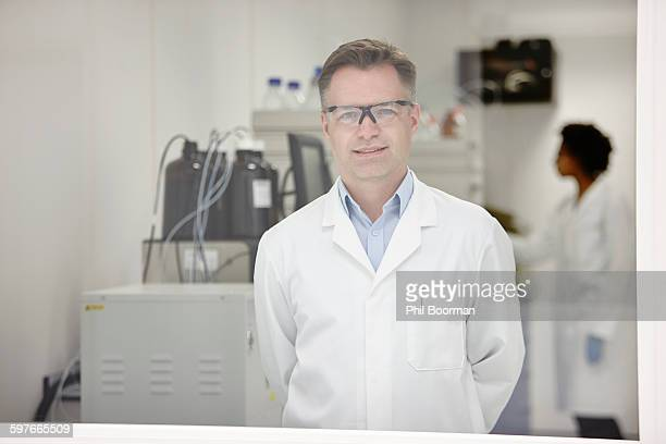scientist smiling in laboratory, colleague working in background - abertillery stock photos and pictures