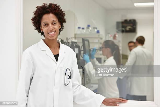 Scientist smiling in laboratory, colleagues working in background