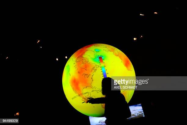 A scientist standing in front of a globe delivers a speech at the Bella Centre during the United Nations Climate Change Conference in Copenhagen on...