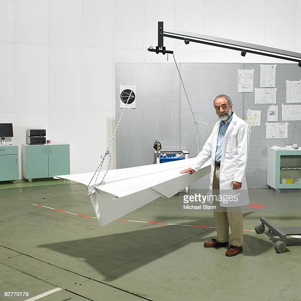 Scientist standing in laborator with paper plane