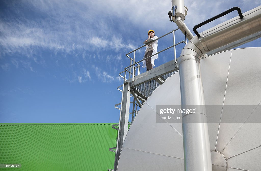 Scientist standing on walkway on tanks : Stock Photo