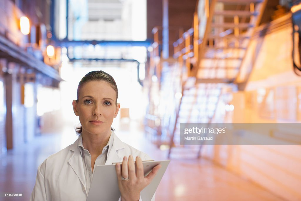 Scientist standing with clipboard in factory : Stock Photo