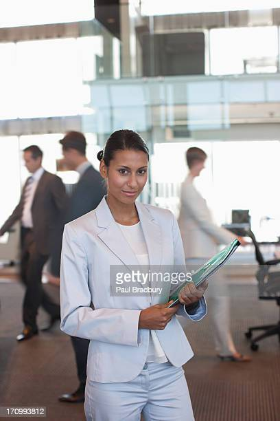 Scientist standing with folder in office