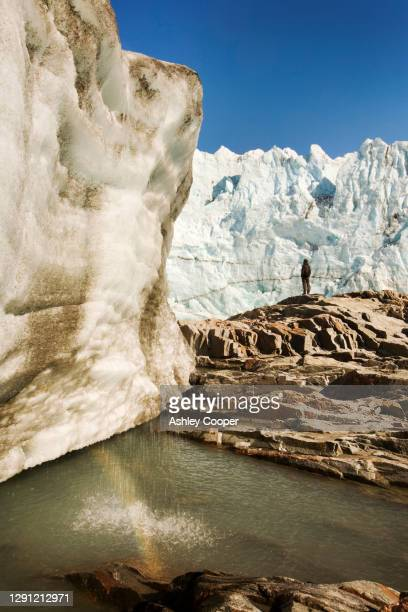 a scientist studying the russells glacier draining the greenland icesheet inland from kangerlussuaq on greenlands west coast. - glacier collapsing stock pictures, royalty-free photos & images