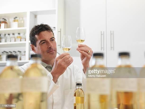 scientist tasting whisky in plant - bebida destilada - fotografias e filmes do acervo