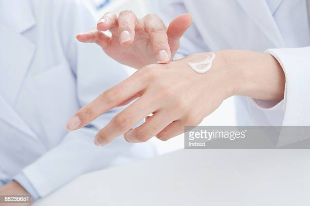 Scientist testing and applying cream on hand