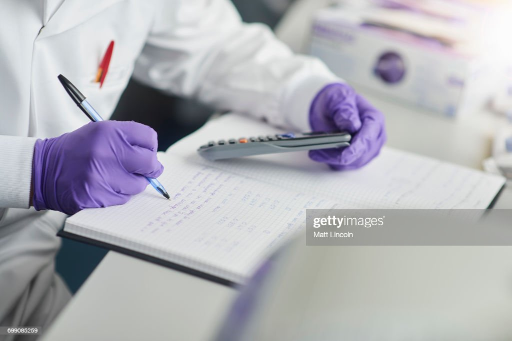 Scientist using calculator writing in notebook : Stock Photo
