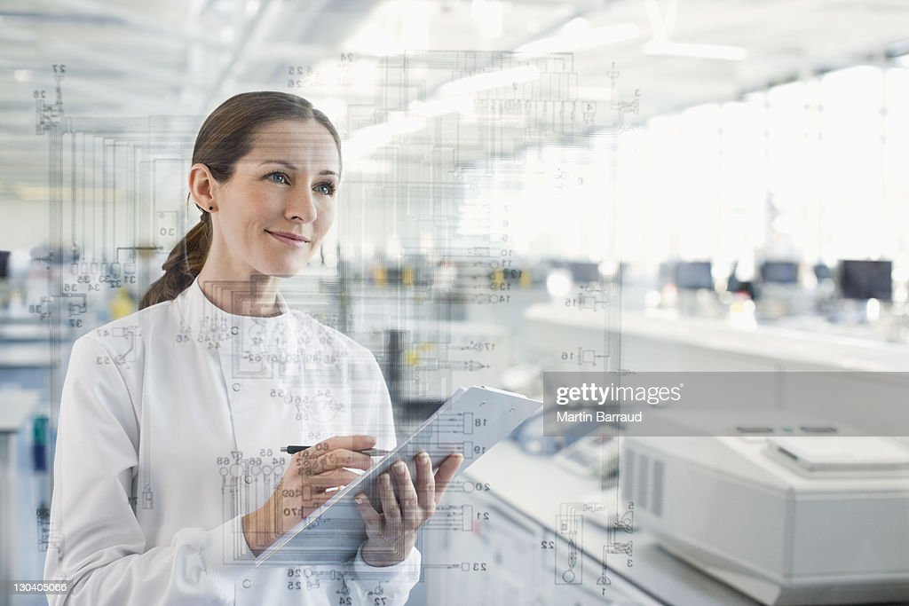 Scientist using clipboard and touch screen in lab : Stock Photo