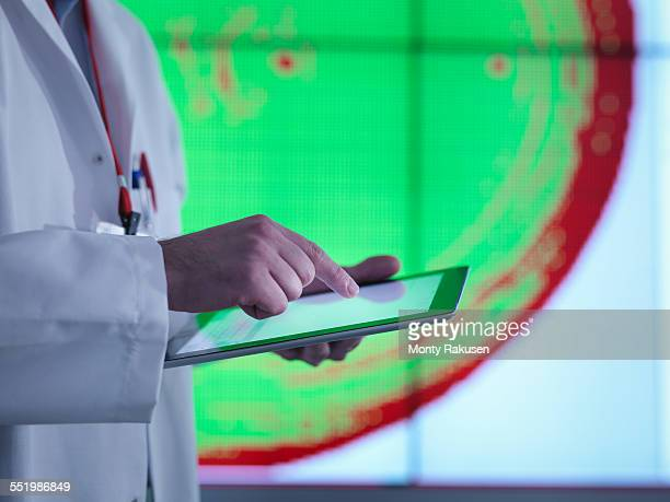 Scientist using digital tablet in front of graphical display of silicon wafer on screens, close up