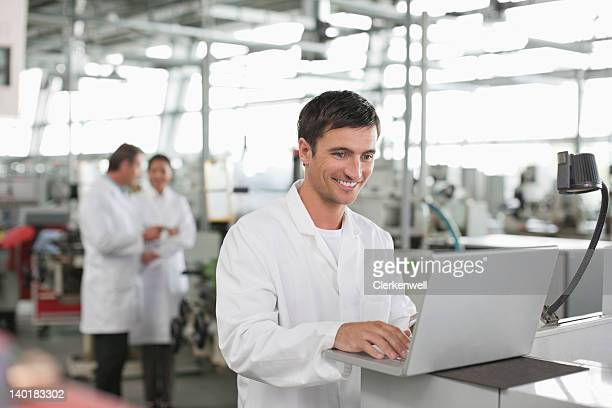 Scientist using laptop in laboratory