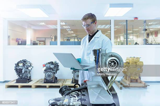Scientist using laptop in turbo charger automotive research laboratory