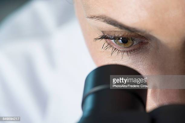 Scientist using microscope, close-up