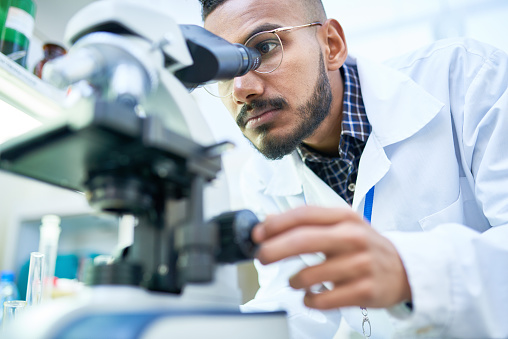 Scientist Using Microscope in Laboratory 909176662