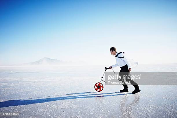 Scientist using surveyors wheel on salt flat