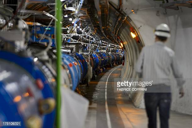 A scientist walks in a tunnel inside the European Organisation for Nuclear Research Large Hadron Collider during maintenance works on July 19 2013 in...