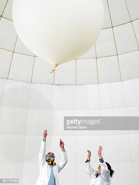 scientist watch balloon float away - weather balloon stock pictures, royalty-free photos & images