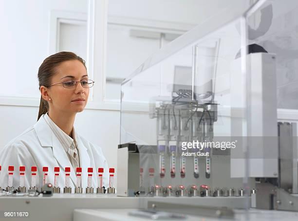 Scientist watching test tubes in machine