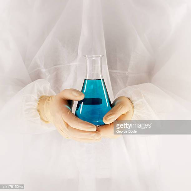 scientist wearing a fully protective suit holding a flask with blue liquid - frasco cónico fotografías e imágenes de stock