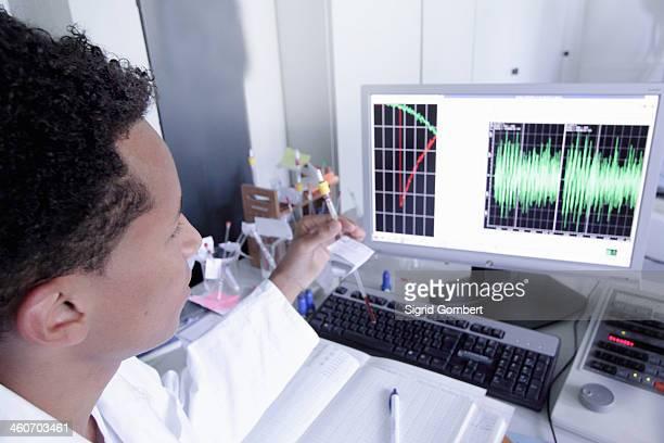 scientist wearing lab coat working on computer - sigrid gombert - fotografias e filmes do acervo