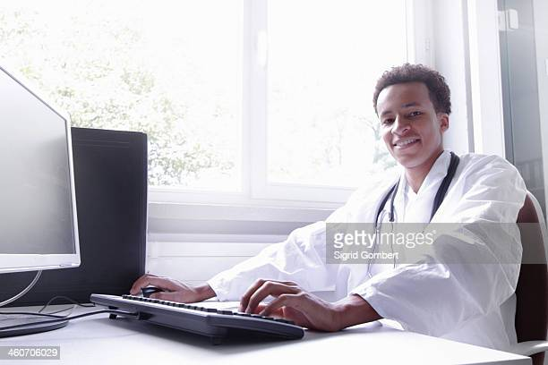 scientist wearing lab coat working on computer - sigrid gombert stock pictures, royalty-free photos & images