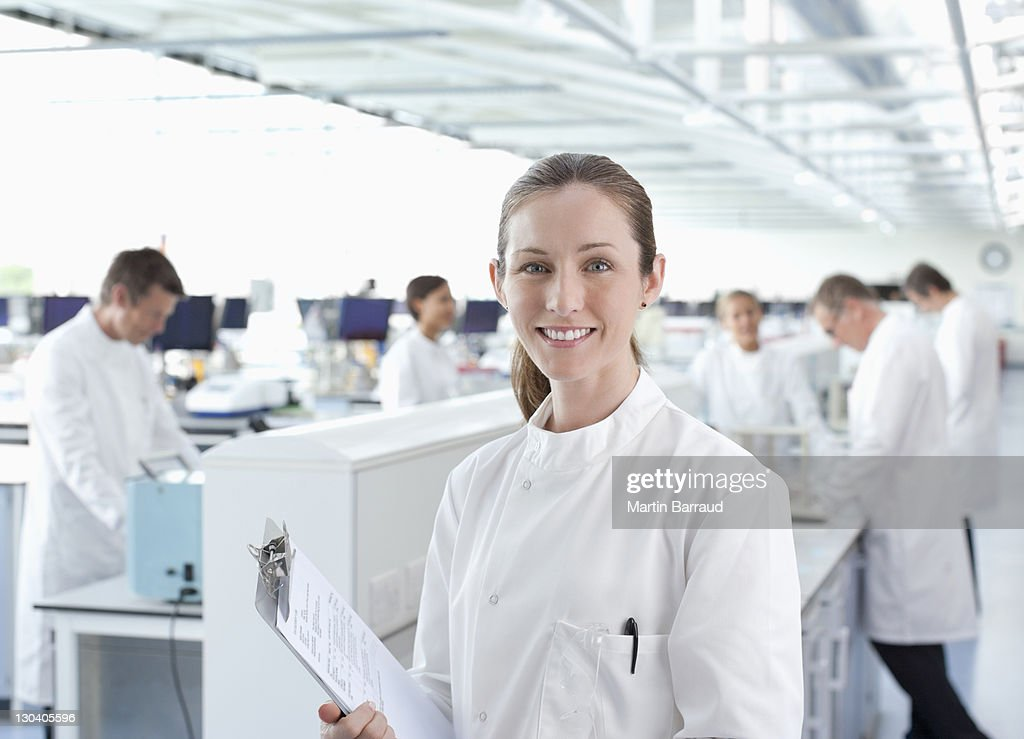 Scientist with clipboard in lab : Foto stock