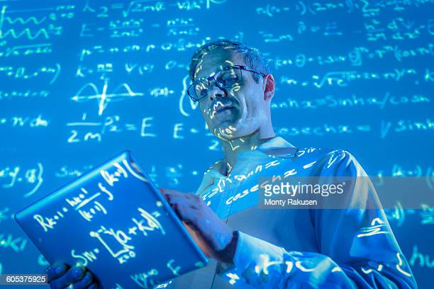 Scientist with digital tablet and projected mathematical data