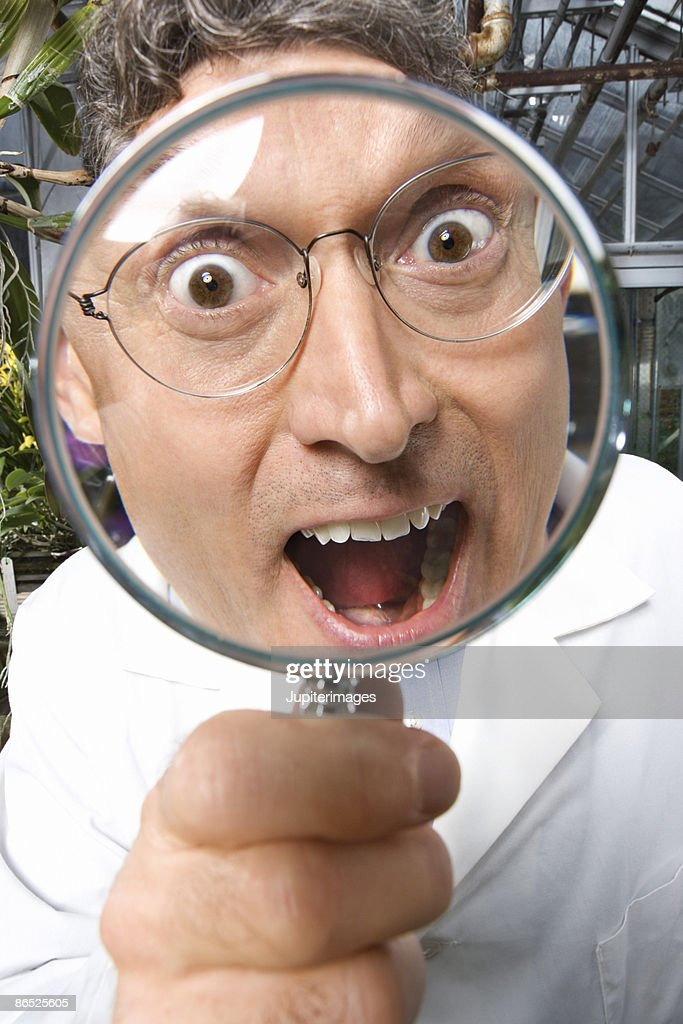 Scientist with magnifying glass : Stock Photo