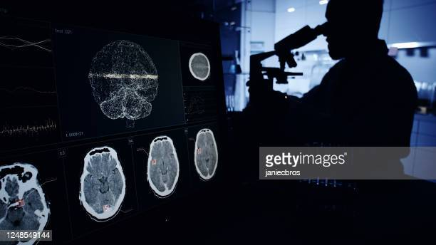 scientist with microscope. brainwave scanning research on computer screens - human body part stock pictures, royalty-free photos & images