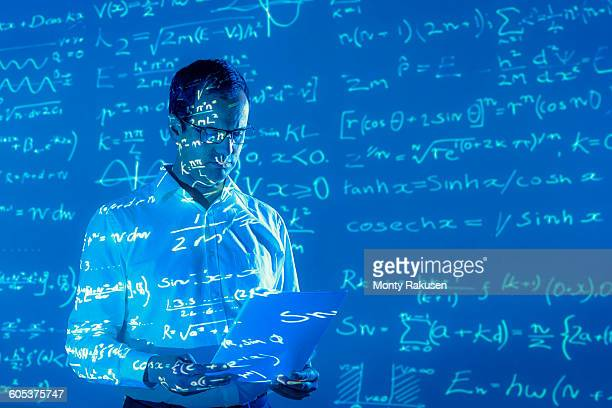 Scientist with projected mathematical data