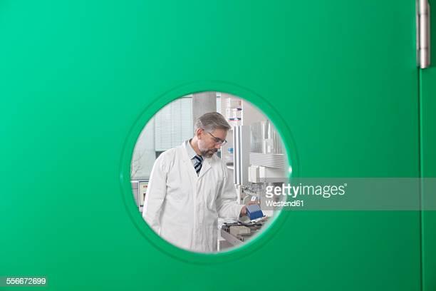 Scientist working behind green door