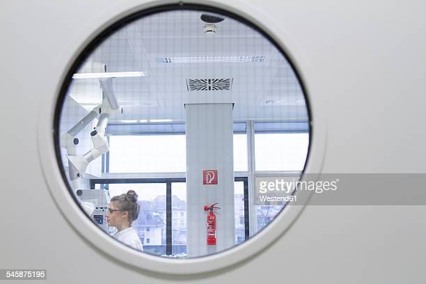 Scientist working in laboratory behind safety door