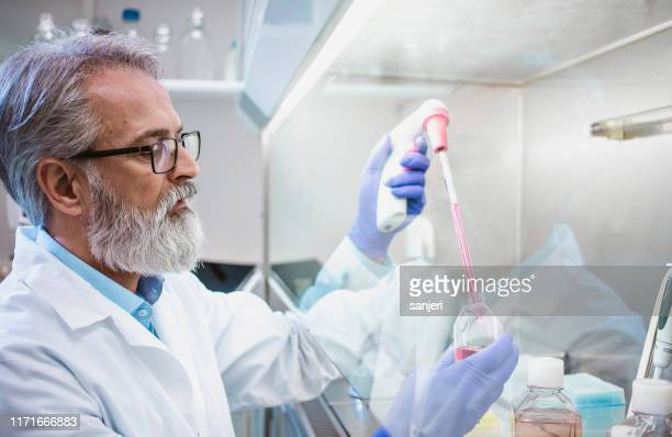 scientist working in the fume hood - volume fluid capacity stock pictures, royalty-free photos & images