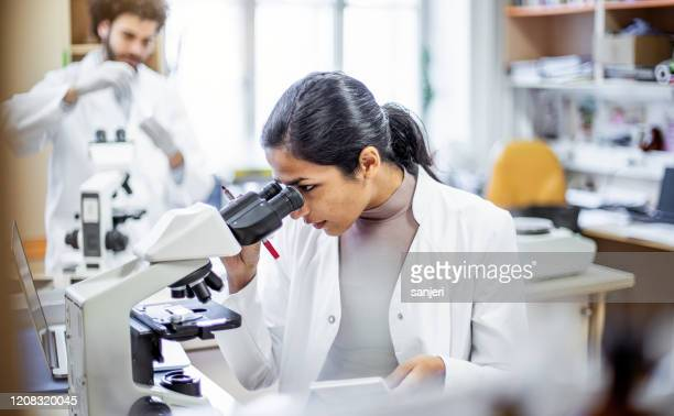 scientist working in the laboratory, looking through a microscope - microbiologist stock pictures, royalty-free photos & images