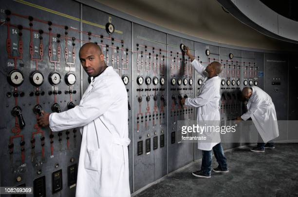 Scientist Working with Switchboard in Control Room