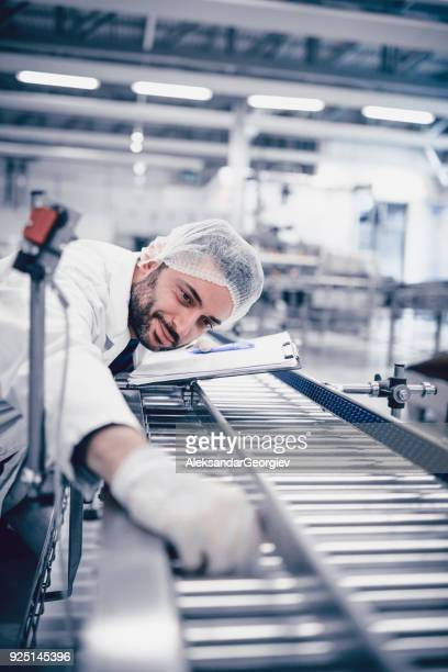 Scientist Writing on Clipboard and Working on Production Line