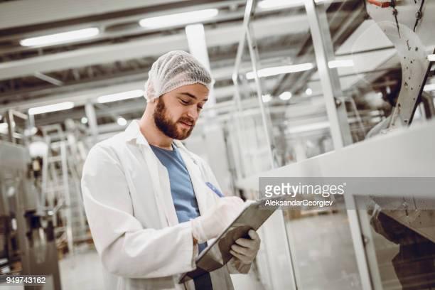 Wissenschaftler schreiben in Zwischenablage und Arbeit am Fließband