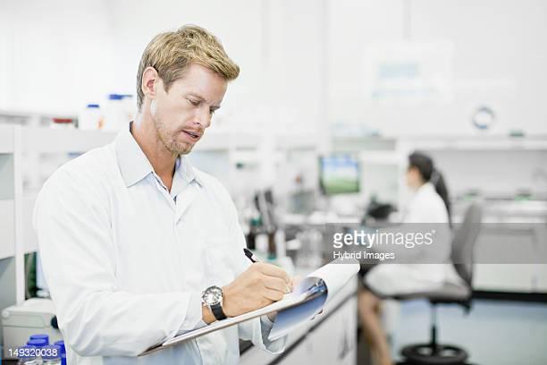 scientist writing on clipboard in lab - klemmbrett stock-fotos und bilder