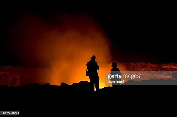 scientists are looking into the glowing lava-lake of erta ale - shield volcano stock pictures, royalty-free photos & images